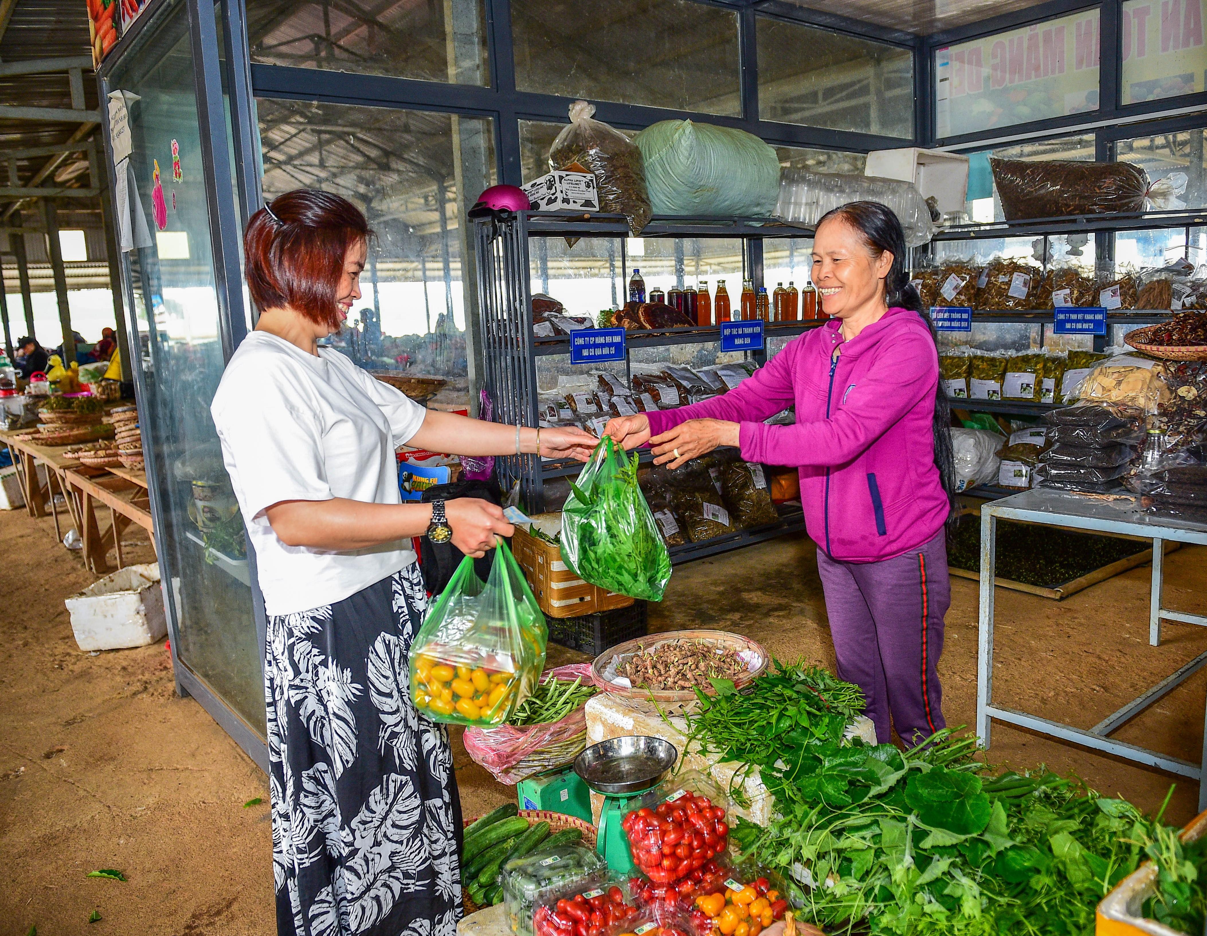 Chị Phan Thị Thanh Hoa (bên phải) bán rau cho khách tại chợ trung tâm huyện Kon Plông